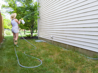 Woman hosing down the sides of her house