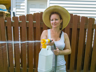 Attractive woman in a hat using a pressure sprayer