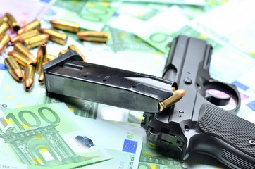Pistol handgun, loaded magazine and bullets on euro banknotes background