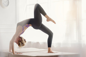 Slim flexible woman doing complex of yoga exercises