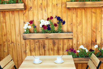 Empty wooden coffee terrace with flower pots table and chairs