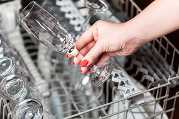 Close up shot of woman's hand taking out clean dishes from dishwasher machine.