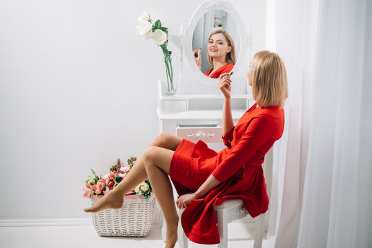 Fashion and business style. Perfect make-up. Sexy woman put on lipstick at mirror. Look of sexy girl or business lady with makeup. Beauty salon or boudoir. Trendy cosmetics and skincare.