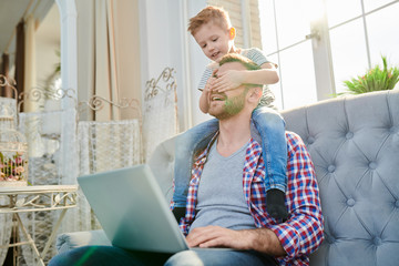Portrait of cute little boy covering eyes of handsome dad using laptop while sitting on his shoulders and playing at home in sunlight