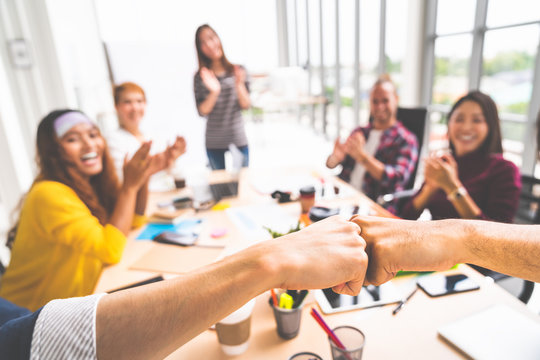 Business partners or men coworkers fist bump in team meeting, multiethnic diverse group of happy colleagues clapping hands. Teamwork cooperation, team building, or success business project concept