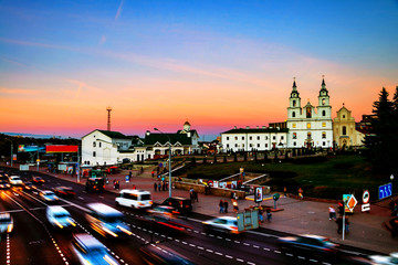 Aerial view of Minsk Cathedral with people and car traffic. Car trail lights and sunset sky.