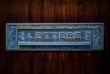 Vintage italian metal mailbox in wooden door, text lettere