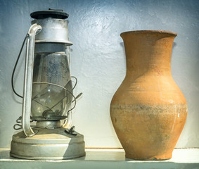 Antique objects of everyday life: a kerosene lamp and a pitcher.
