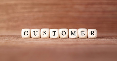 Word CUSTOMER made with wood building blocks