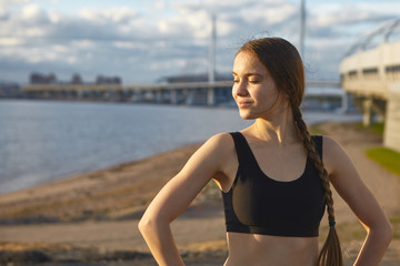 Waist up shot of attractive gorgeous young sportswoman with athletic slim body enjoying warm summer sun during morning training outdoors, smiling and closing eyes, vast river in background