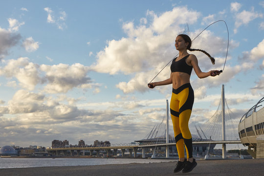 People, healthy lifestyle, activity, sports and fitness concept. Picture of happy endurant sporty girl with long braid jumping with skipping rope outdoors, practicing endurance and stamina