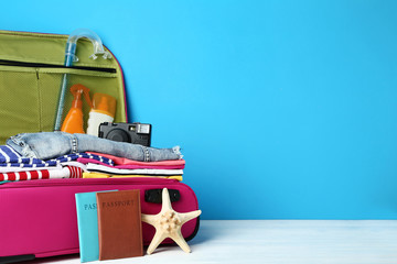 Opened suitcase with clothes, camera and sunscreen bottles on wooden table