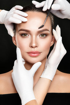 Beautiful woman portrait with classical make up and hands in medical gloves with cosmetic tool.