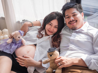 Asian man husband take care of his pregnant wife.Beautiful pregnant woman and her handsome husband are smiling while spending time together.
