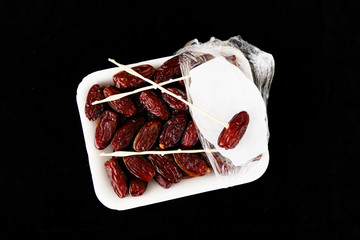 Stock Video of a pack of dates, on a black background, close