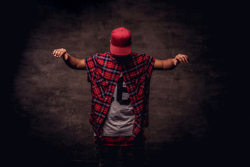 Portrait of an African-American dancer guy dressed in a red fleece shirt and cap at the studio. Isolated on dark textured background.