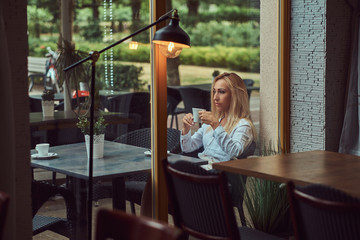 Portrait of a beautiful blonde female dressed in a white blouse sitting at a table holds a cup of coffee at terrace cafe.