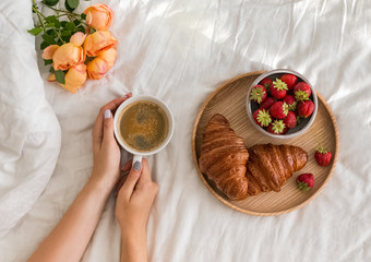 Woman's hands holding a cup of coffee on the bed with white bedsheet.