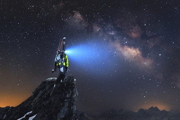 Night landscape. A professional backcountry skier with a backpack and skis stands on a rock in the mountains and shines with a headlamp in the Milky Way