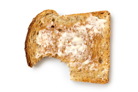 Buttered slice of whole wheat toast isolated on white from above. Bite missing.