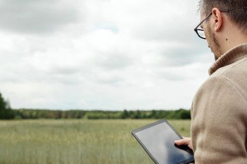 Man A farmer standing in the field and using a tablet. Modern application of technologies in agricultural activities. Farmland, new technologies, harvesting, fertilization, crop inspection.