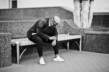 Stylish arabian muslim boy with originally hair and sunglasses posed on streets, sitting on bench.