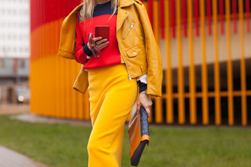 Street, bright style. A young woman in orange jacket, yellow skirt, white sneakers, Sunglasses with a handbag and mobile. Details.