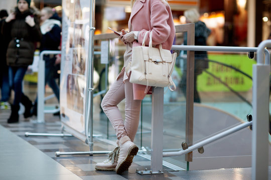 Mall, bright style. Young woman, everyday style, pink panto, pink pants, white handbag, bag, blouse, bracelet. Details.