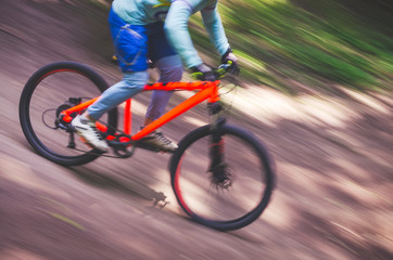 The cyclist descends from the mountain on an orange bicycle, motion blur