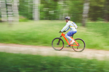 A cyclist in a helmet rides through the forest on a bicycle path, motion blur
