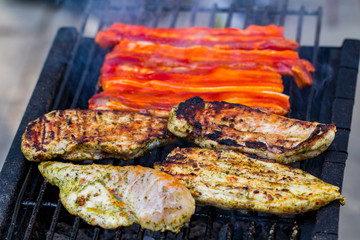Assorted mixed grill from chicken meat, and pork, sausages  roasting on barbecue grid cooked for summer family dinner