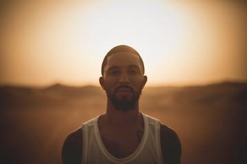 Man standing in desert at sunset