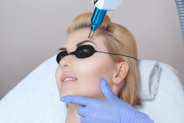 Laser tattoo removal on woman's eyebrows in a beauty salon