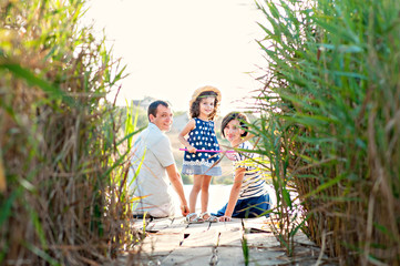 Parents with a beautiful little daughter are sitting on the pier by the lake among the reeds