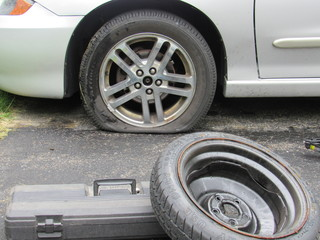 A flat tire with a tool box, spare tire, and car jack