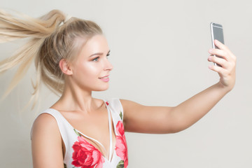 Glamor blonde woman pwith hair in motion making selfie on mobile phone against a grey background