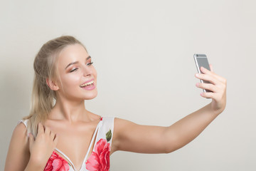 Charming cute girl making self portrait on smartphone against a grey background