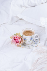 white bed, fresh coffee and pink roses. Good morning Vintage photo. copy space.