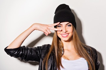 Teenage girl in black leather jacket and beanie hat posing a smiling. Studio portrait, mild retouch