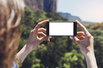 Hipster blogger girl holds mobile phone in female hands, take photo picture of natural landscape on a sunny summer day while travel and vacation, clean blank screen cellphone on background mount