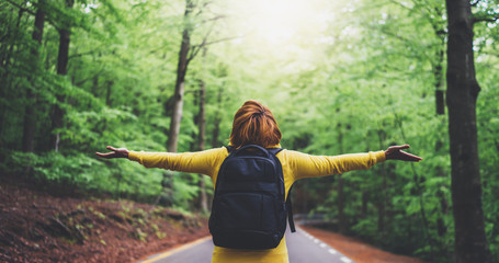 Wall Mural - tourist traveler with backpack with raised hands, girl hiker view from back looking into road at forest with arms outstretched and enjoying the breath of fresh clean air in trip, relax holiday concept
