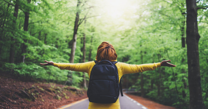 tourist traveler with backpack with raised hands, girl hiker view from back looking into road at forest with arms outstretched and enjoying the breath of fresh clean air in trip, relax holiday concept