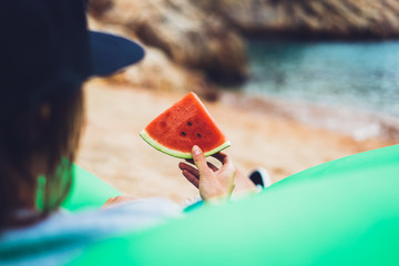 young girl hipster relax on beach coast and holds in her hand a slice of red fresh fruit watermelon on sea background, woman on seaside eating sweet healthy food, vacation in summer concept