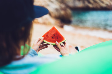 young girl hipster relax on beach coast and holds in her hand a slice of red fresh fruit watermelon on blue sea background, woman on seaside nature eating sweet healthy food, vacation in summer