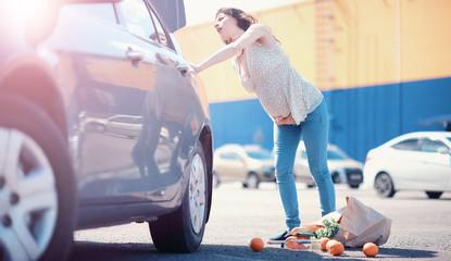 Woman with shopping near car