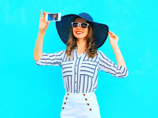 Cool girl  is taking a picture on a smartphone wearing a straw summer hat, white pants over colorful blue background