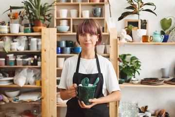 Pretty girl with colorful hair in black apron and white T-shirt holding handmade bowl in hands dreamily looking in camera spending time at modern pottery studio