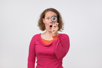 European woman in pink sweater looking through a magnifying glass with opened surprised mouth.