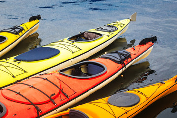 Colorful orange and yellow kayaks floating in the blue water