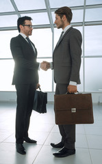 two businessmen shaking hands in the lobby of the office
